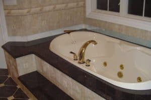 white and gold bathtub sorrounded by a dark stone and light tile