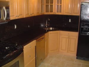 Oak style cabinets with dark granite and full granite backsplash