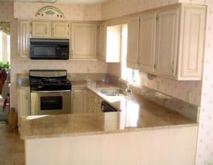 gold handles on cream colored cabinets with black and stailess steel appliances and a light countertop