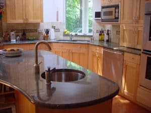 kidney shaped granite island with a stainless steel round sink and faucet with an angled oak shaker kitchen