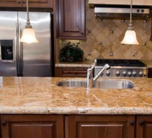 caramel granite countertop and with tile diagonal Backsplash and brown cabinets